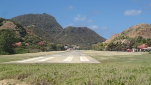 Interesting looking airport nestled between two hills and a mountain at one end. Behind me is the ocean