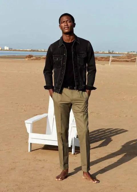 man wearing black denim jacket on brown chinos
