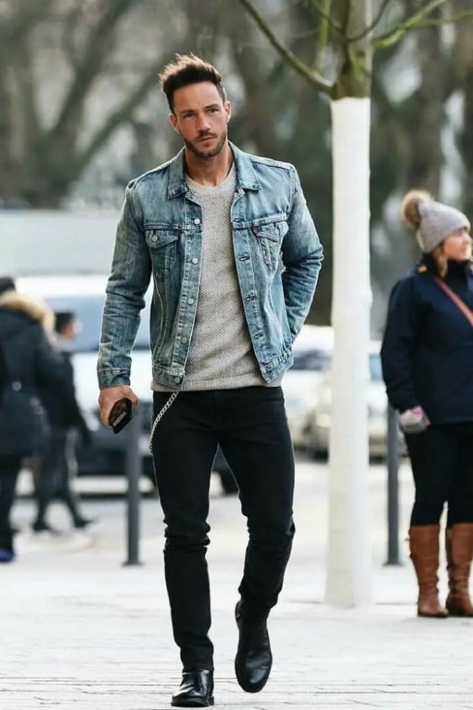 man layering jean jacket on a grey t-shirt