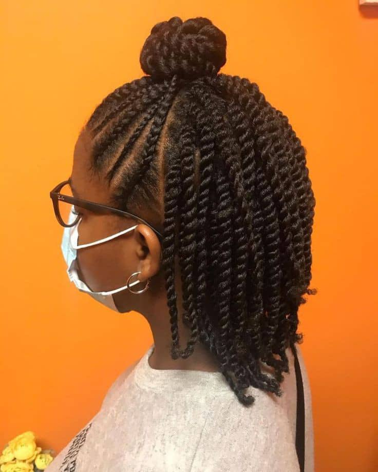 lady with face mask donning cornrows with twists hairstyle