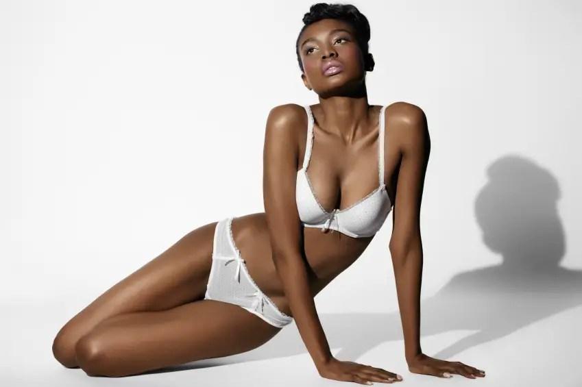 ebony underwear model in pant and bra sitting on the floor