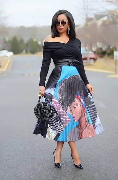 lady in a black top and a colorful pleated midi skirt
