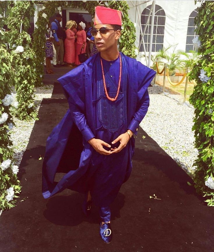 Denola Grey in a blue agbada and red cap