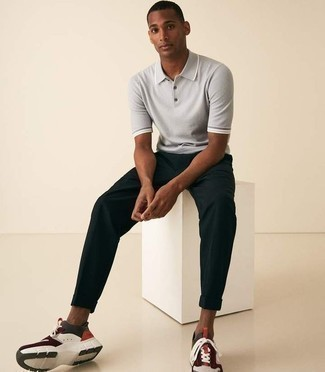 man wearing multicolored shoes, black pants and grey polo