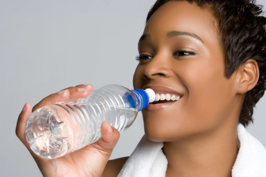 African woman drinking water and smiling