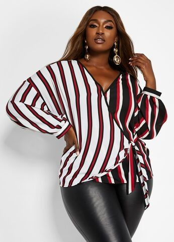 a black lady in a stripped wrap top and black tight pants