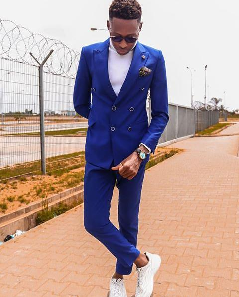 man in blue suit and white sneakers