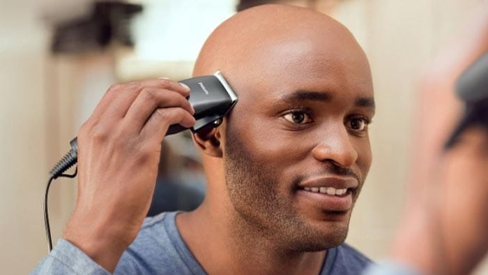 skincut hairstyle on a black man handling a pair of clippers
