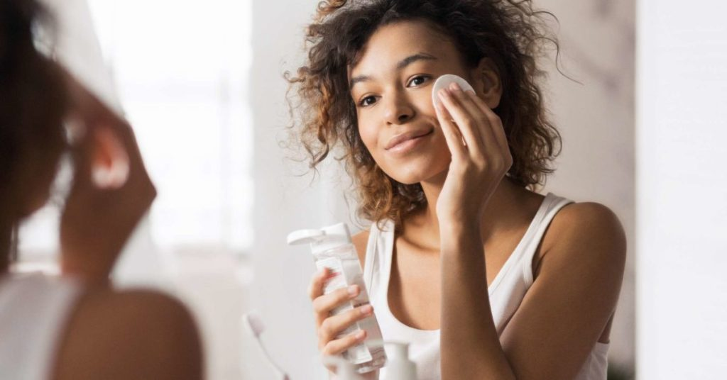 A lady cleaning her face  in front of the mirror