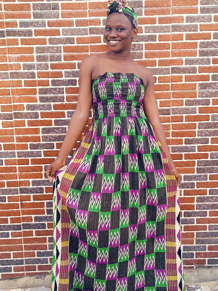 Smiling Victoria B. Willie wearing a kente print gown
