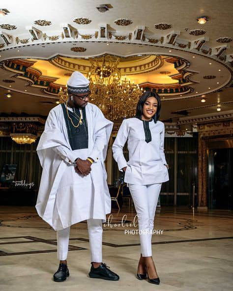 man in white long sleeves agbada with his lady in white senator attire