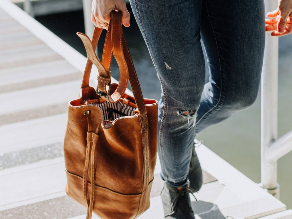 woman carrying a leather bucket bag
