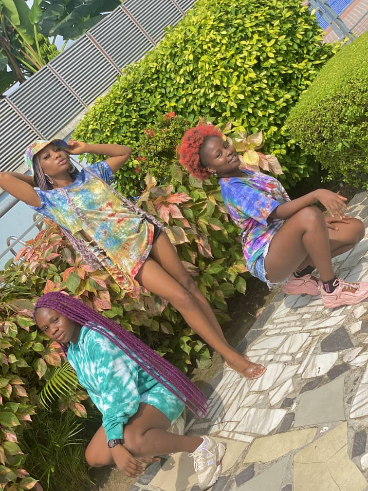 3 ladies wearing adire tops and posing sexily