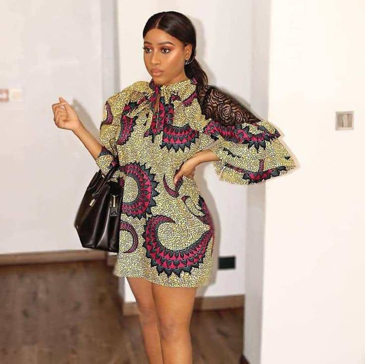 lady wearing beautiful short ankara gown with black bag