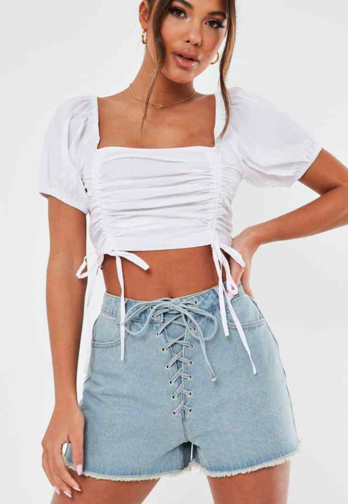 lady wearing a high-waisted jean shorts with white crop top