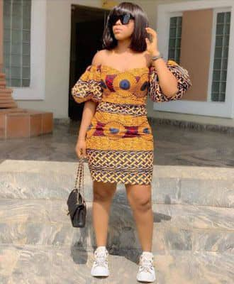 lady rocking ankara short gown with white sneakers