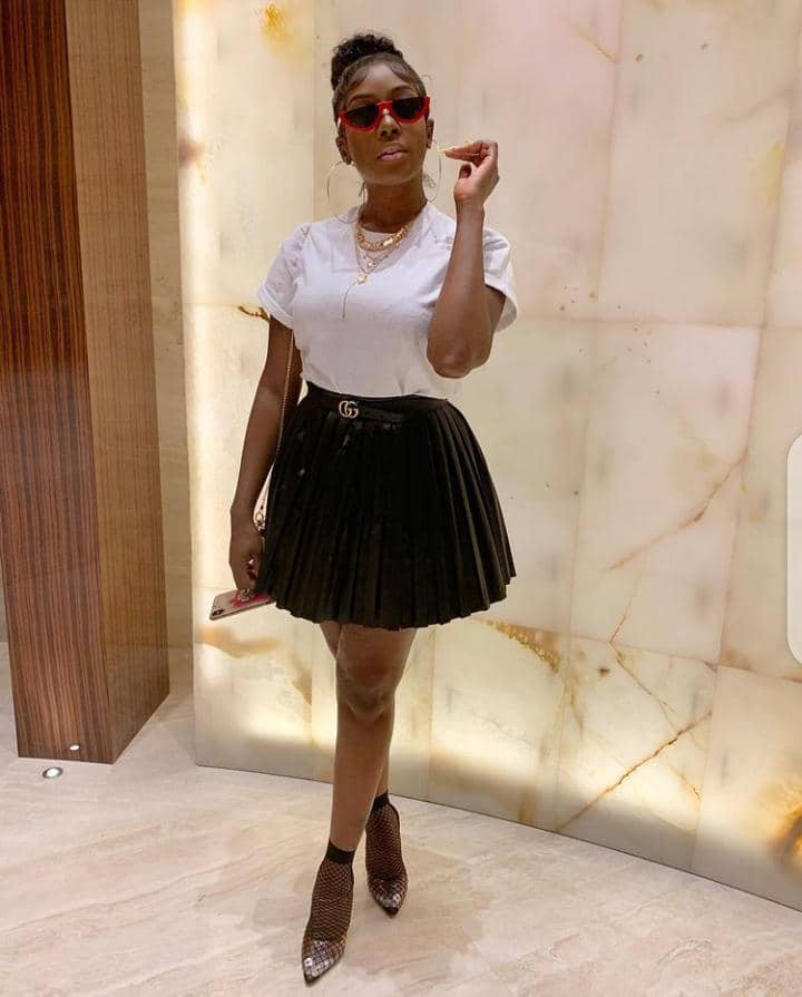lady in a simple white top and short black skirt, ready for her office end of the year party