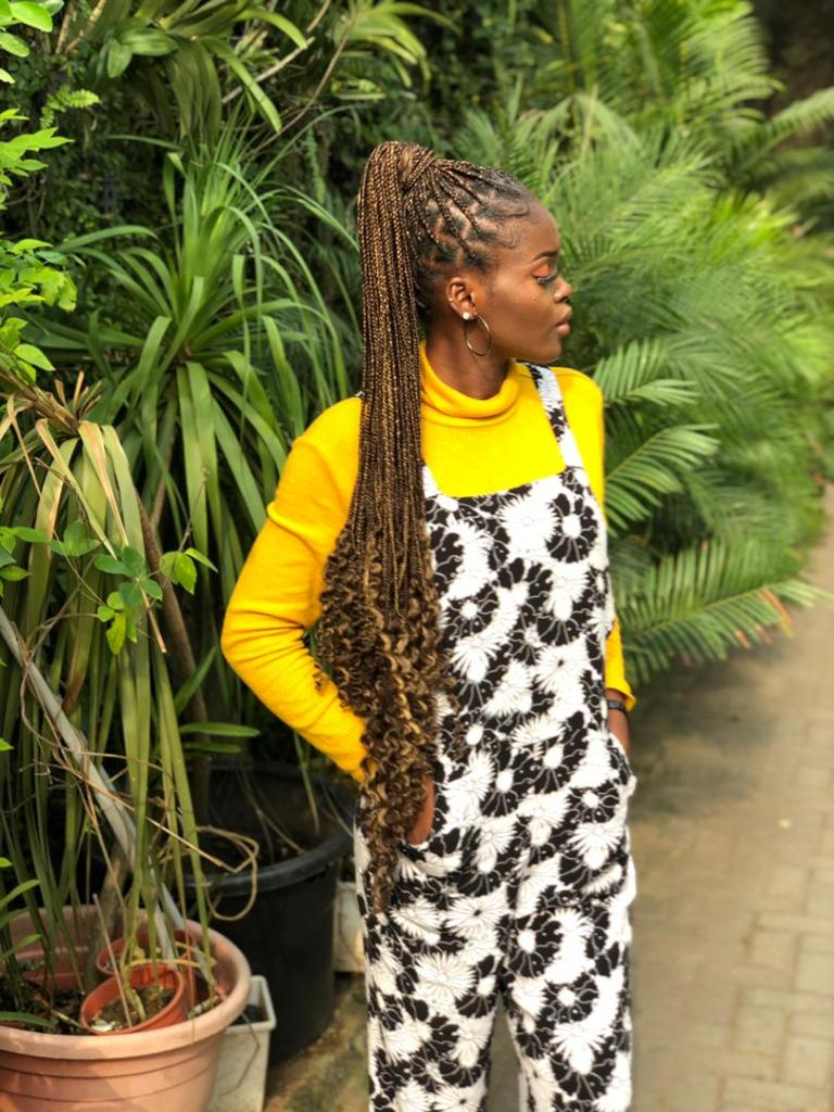 Kije Achu wearing knotless braids with curls