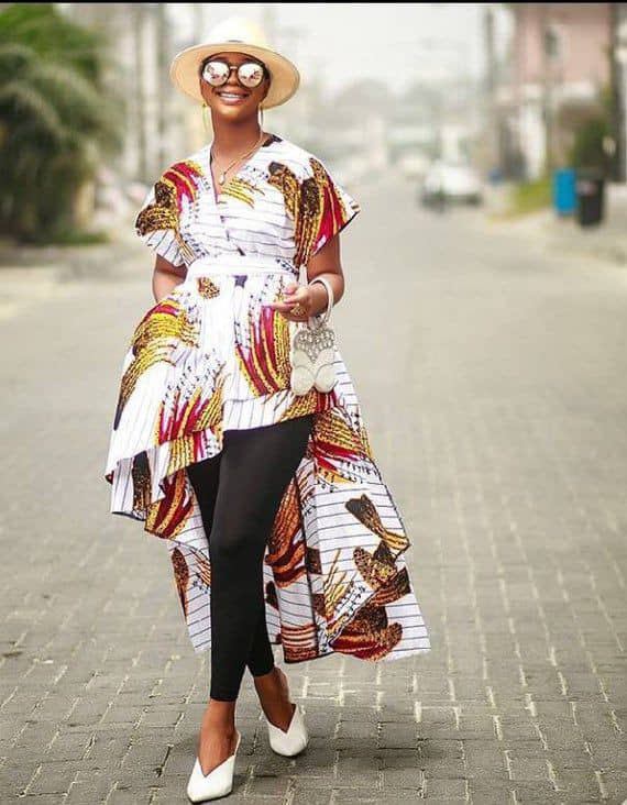 smiling lady wearing ankara high low top with a hat and glasses