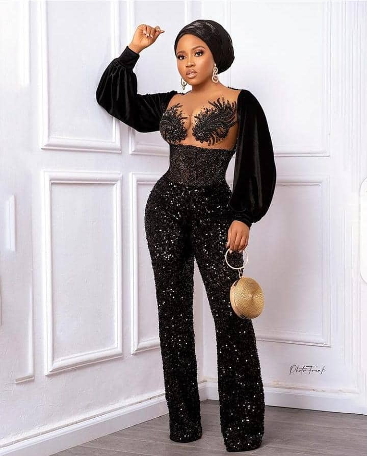 lady rocking black jumpsuit with headtie