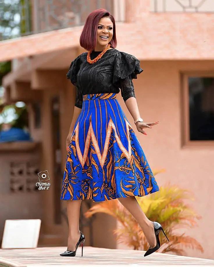 smiling lady wearing black top and ankara flare skirt
