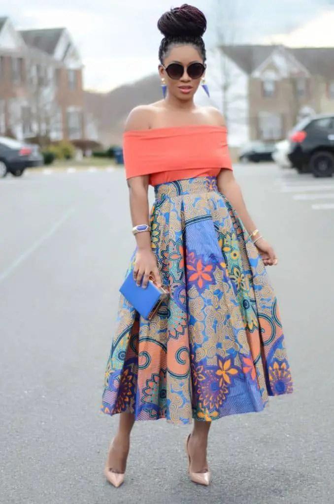 lady wearing orange top and ankara pleated skirt