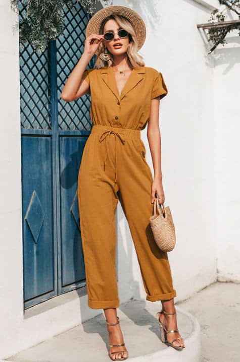 lady wearing brown jumpsuit with hat and glasses
