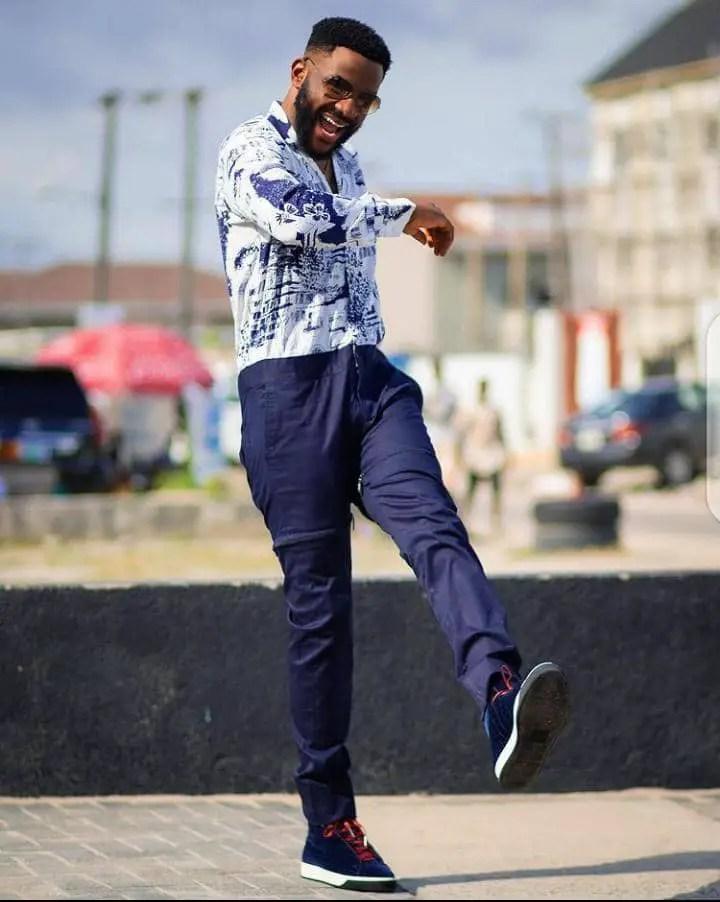 Smiling Ebuka kicking in a colorful shirt