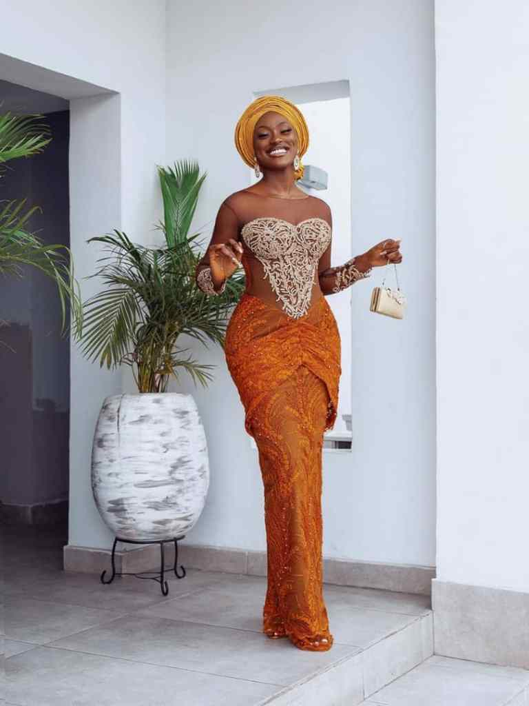 smiling lady wearing lace aso ebi with gele