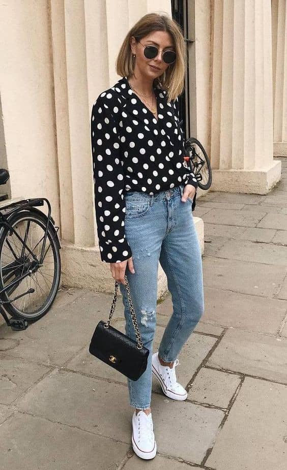 lady wearing white on black polka dot top with jeans