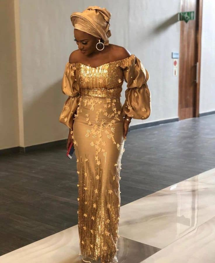 lady inn a gold lace dress with matching gele