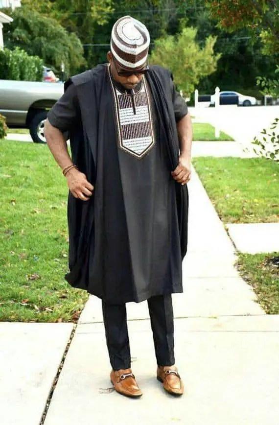 man wearing black agbada with native cap