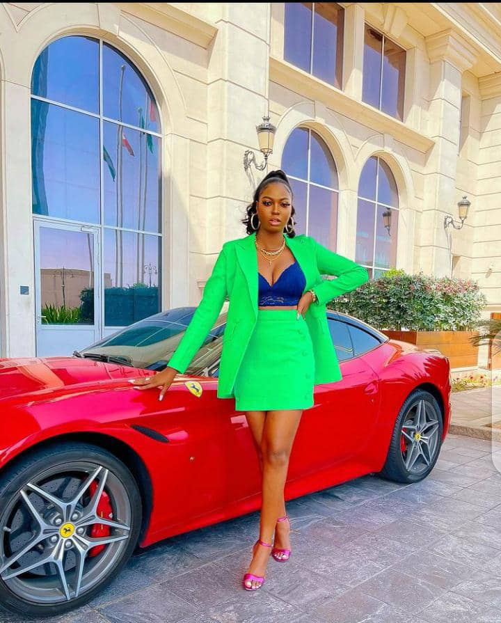 lady wearing green matching set top and mini skirt in front of a red car