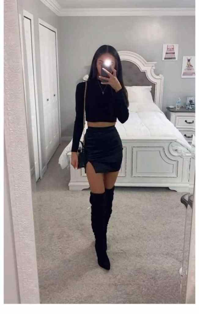 lady wearing black top and mini skirt with knee-high boots