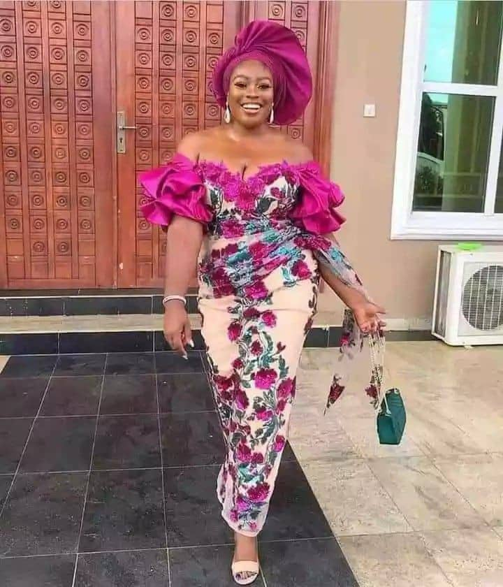 smiling lady wearing lace owambe outfit with gele