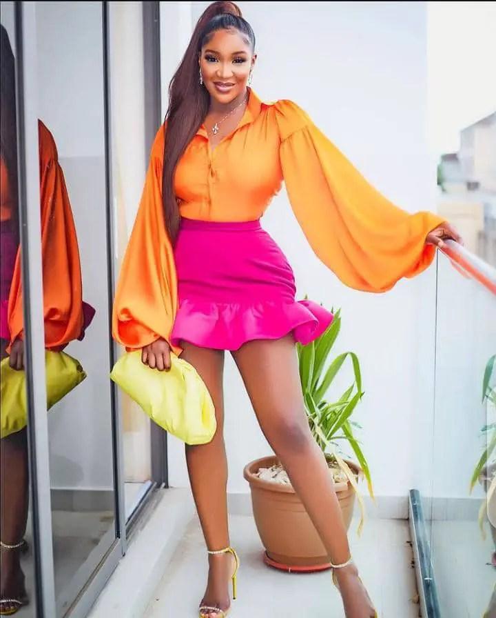 smiling lady wearing orange shirt and pink mini skirt