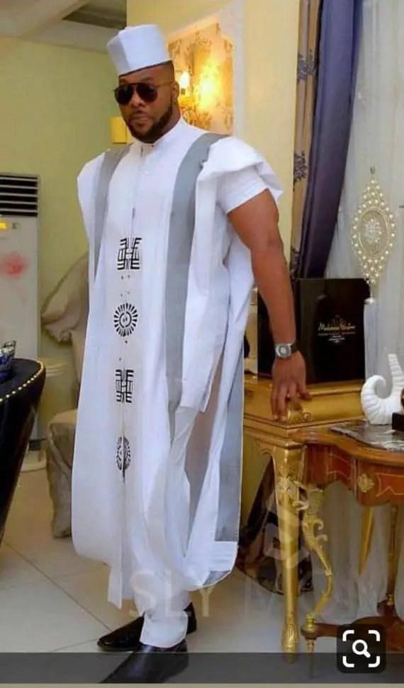 man wearing white agbada with cap