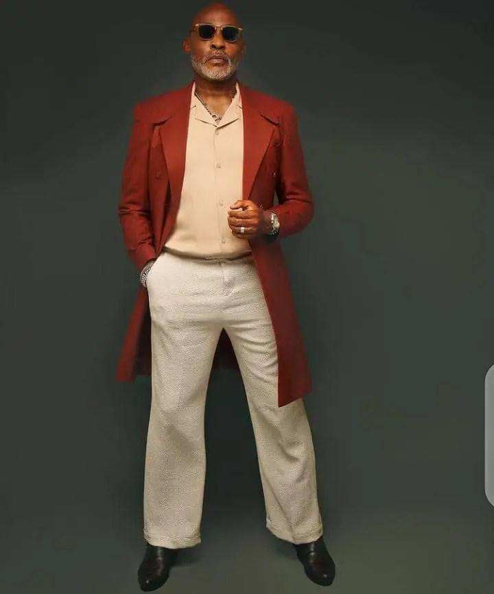 Richard Mofe-Damijo wearing long overcoat