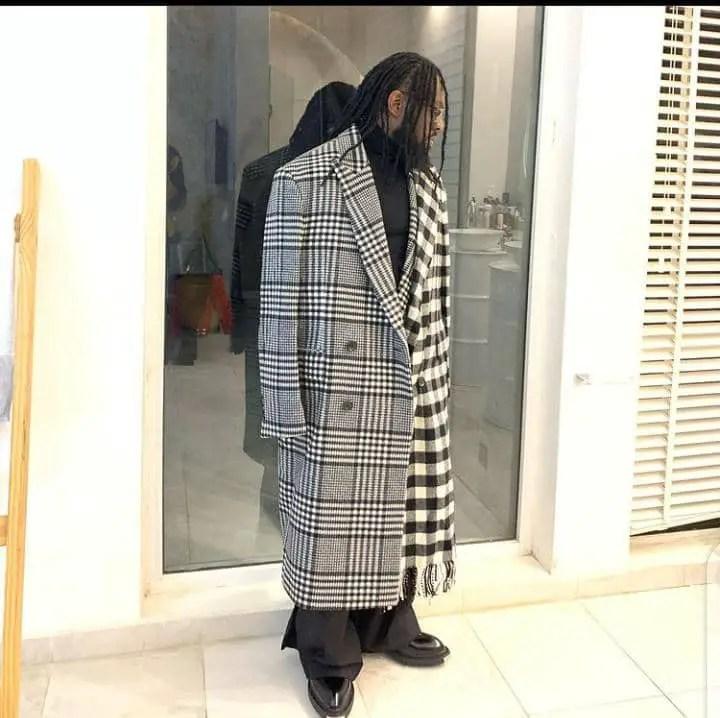 Timaya wearing long overcoat