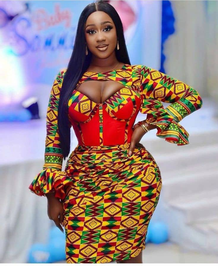 lady wearing colorful African print dress with a touch of red plain material