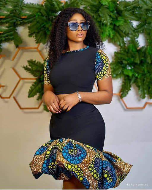 lady wearing plain black material dress with some touches of ankara