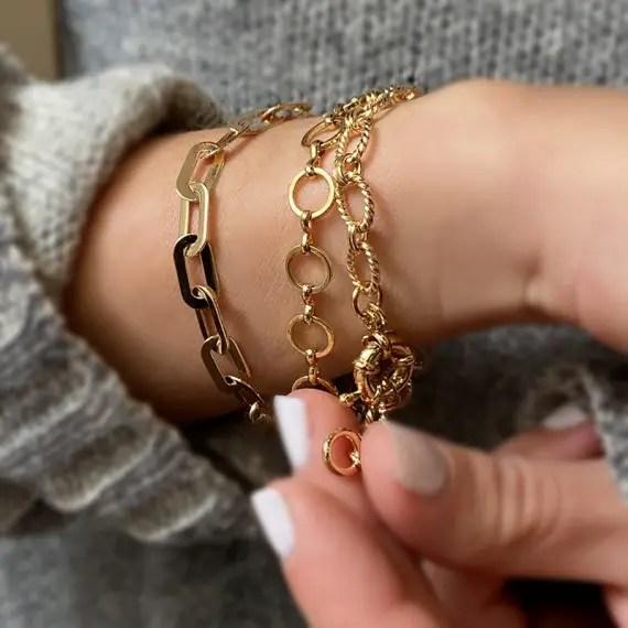 close up shot of lady's arm wearing Oh bracelets