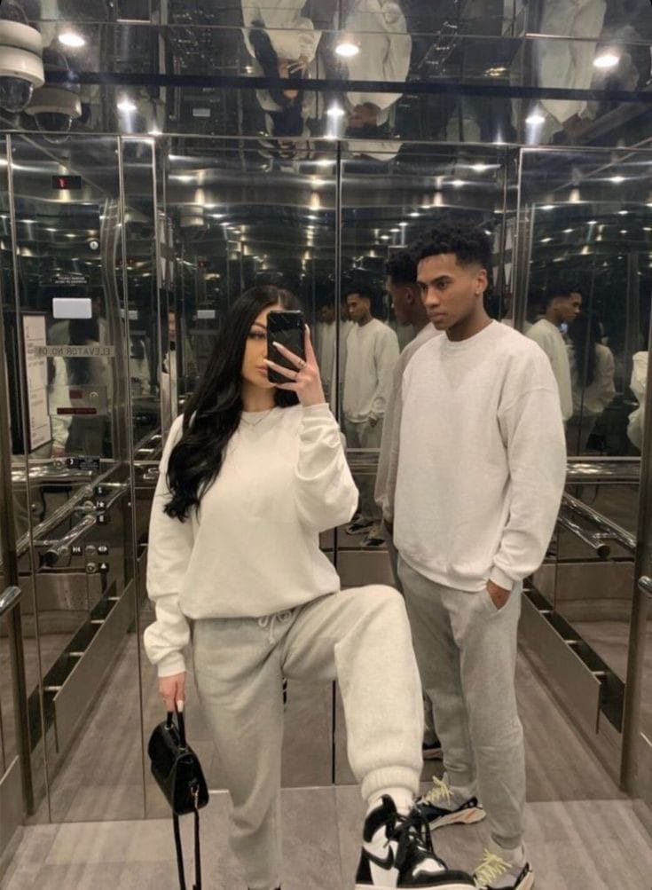 couple wearing matching sweaters and taking elevator picture together