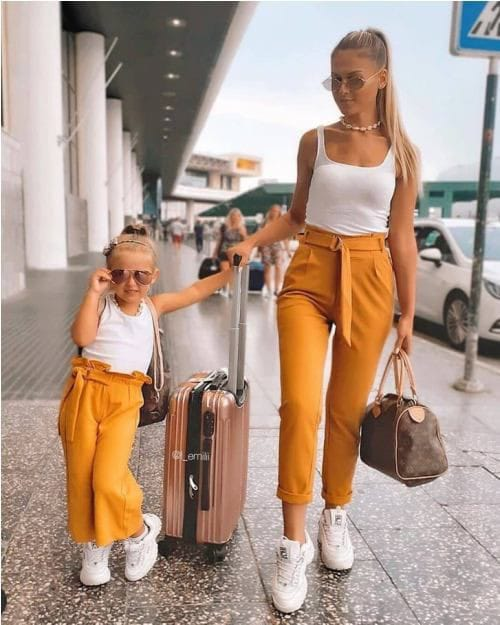 mother and daughter wearing matching tops and pants and sneakers
