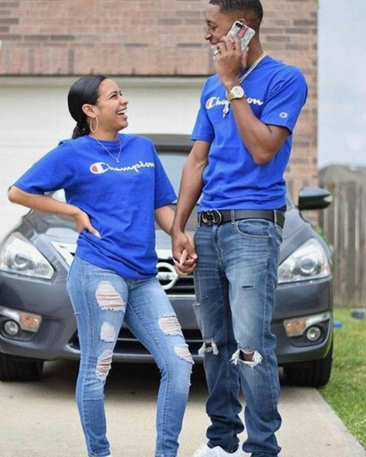 smiling couple wearing matching t-shirts and ripped jeans
