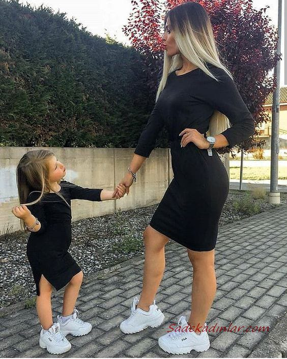 mother and daughter wearing black dress and white sneakers