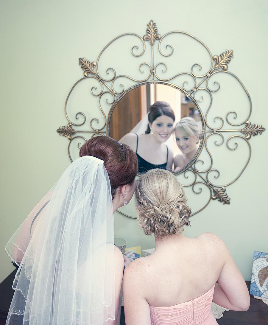 Bride and bridesmaid looking in mirror