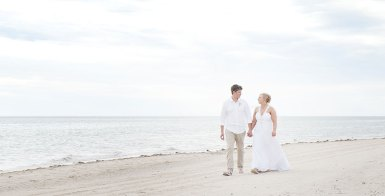 Bride and Groom Walking along Grange Beach
