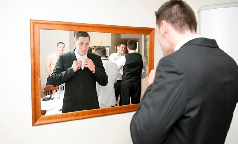 Groom putting on tie in mirror
