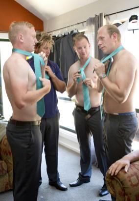 Groomsmen putting on ties